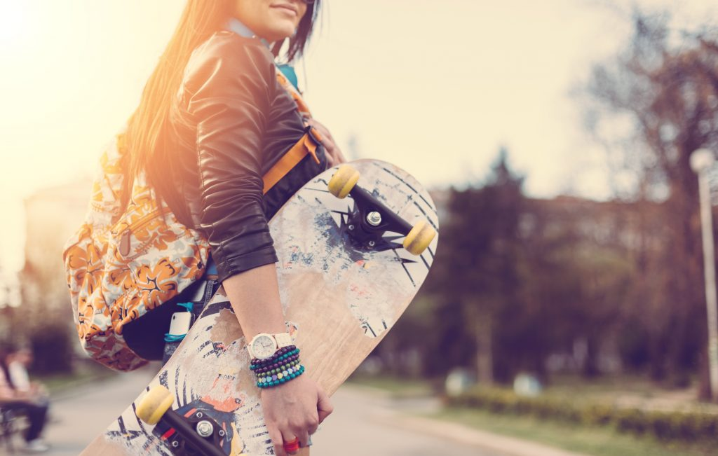Teenage girl with skateboard in the park