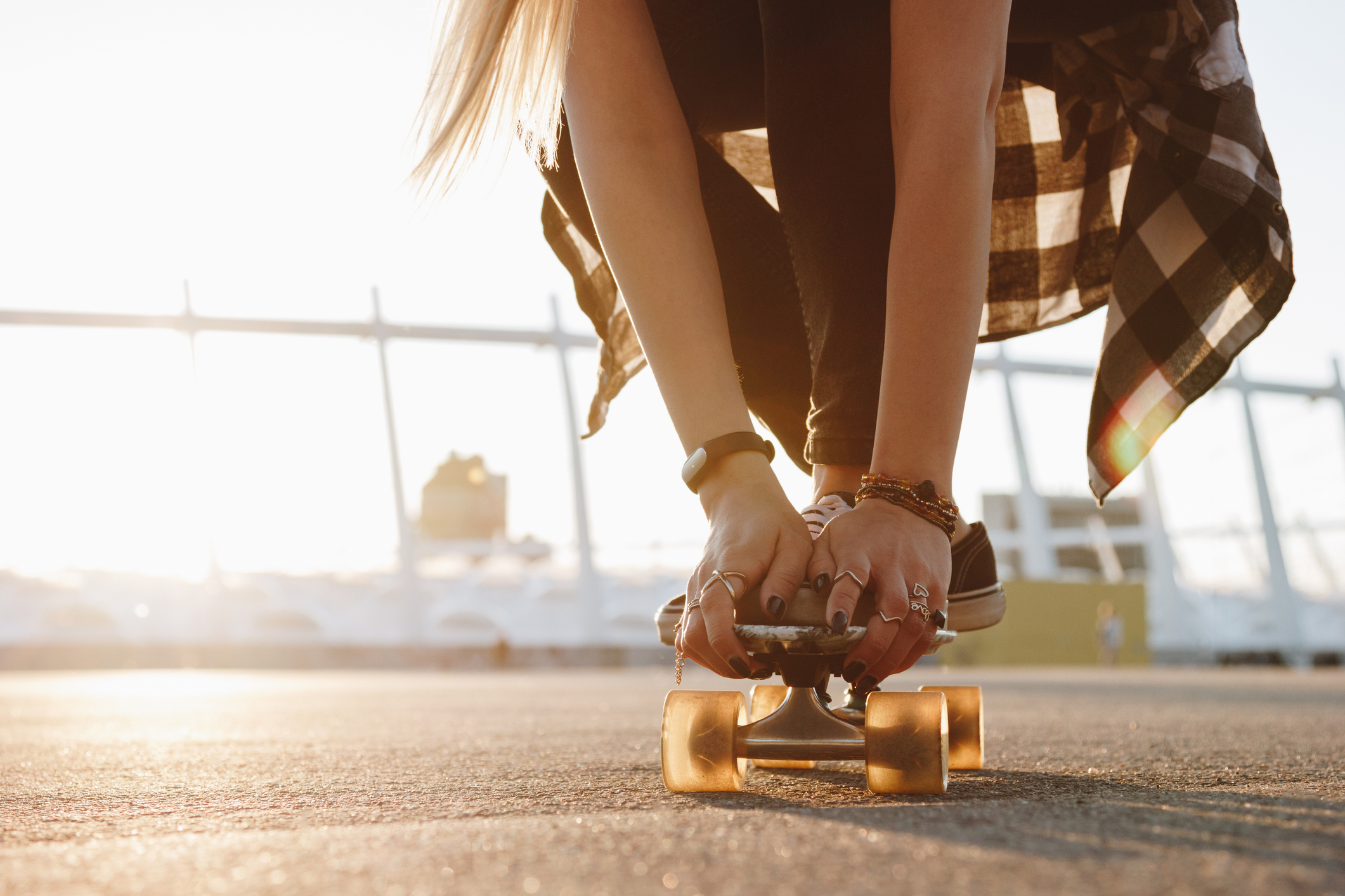 Hipster girl legs and hands with rings on a skate board