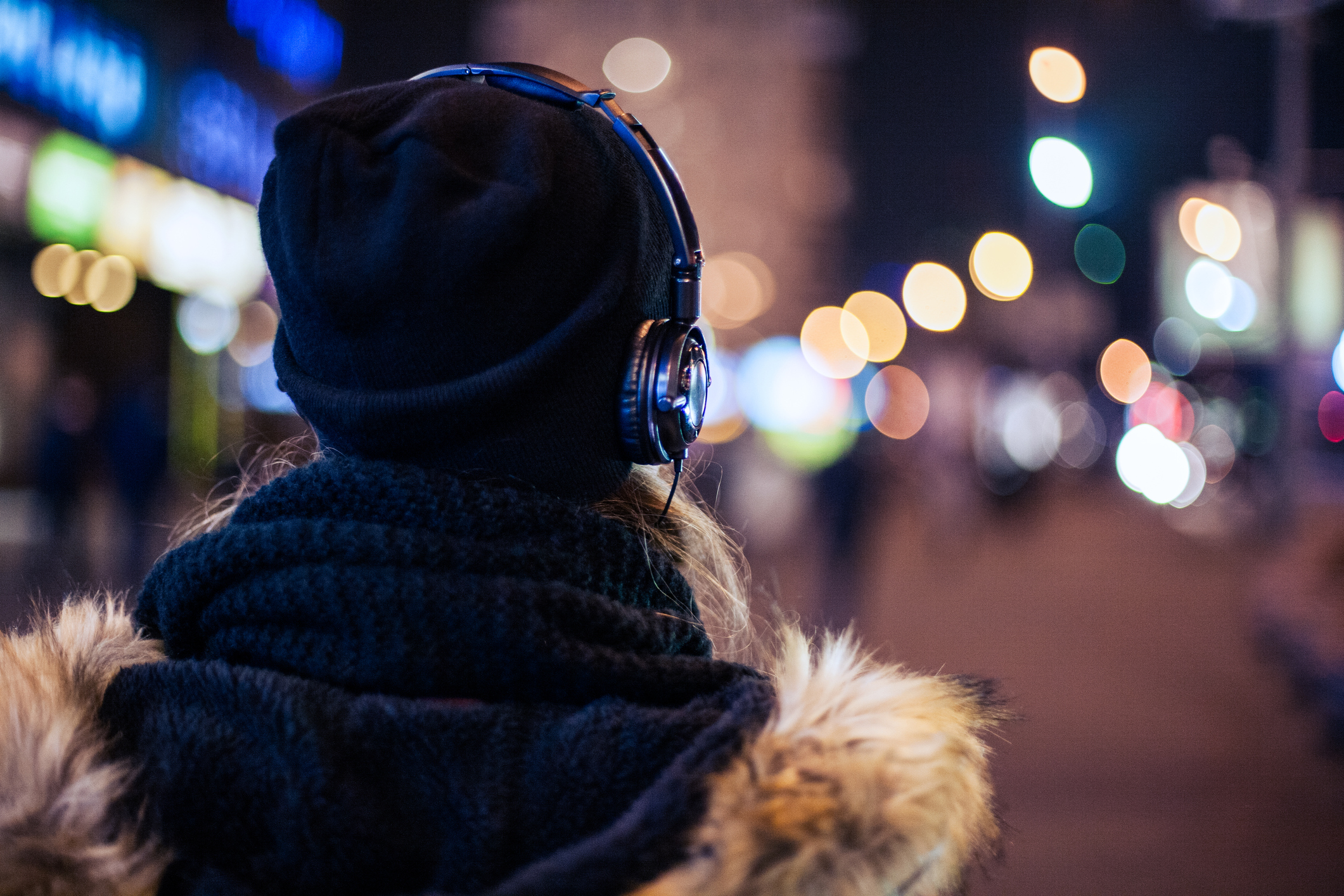 Girl walking through night city street listening to the music