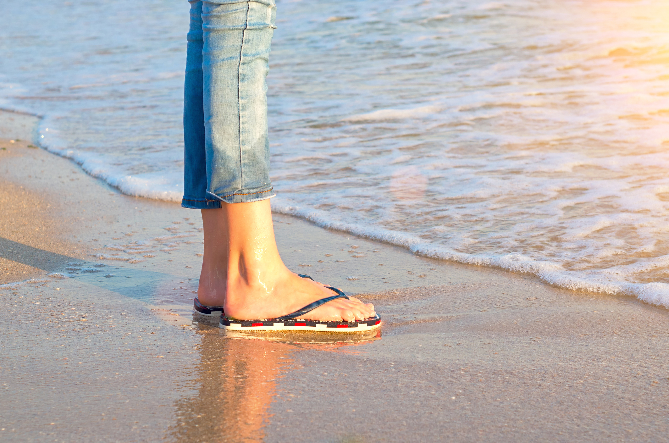 legs of a girl in jeans and sandals in a sea wave, sunlight