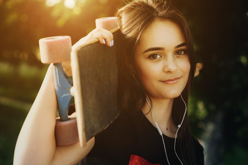 Portrait of a young woman holding a skateboard on her neck and looking at camera.