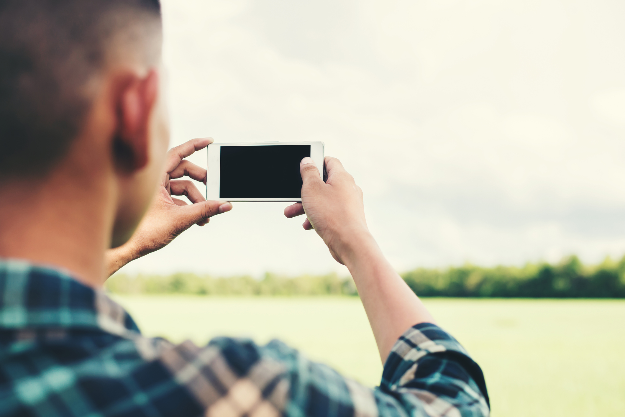 Young hipster man using smartphone taking the landscape photography in the grassland.