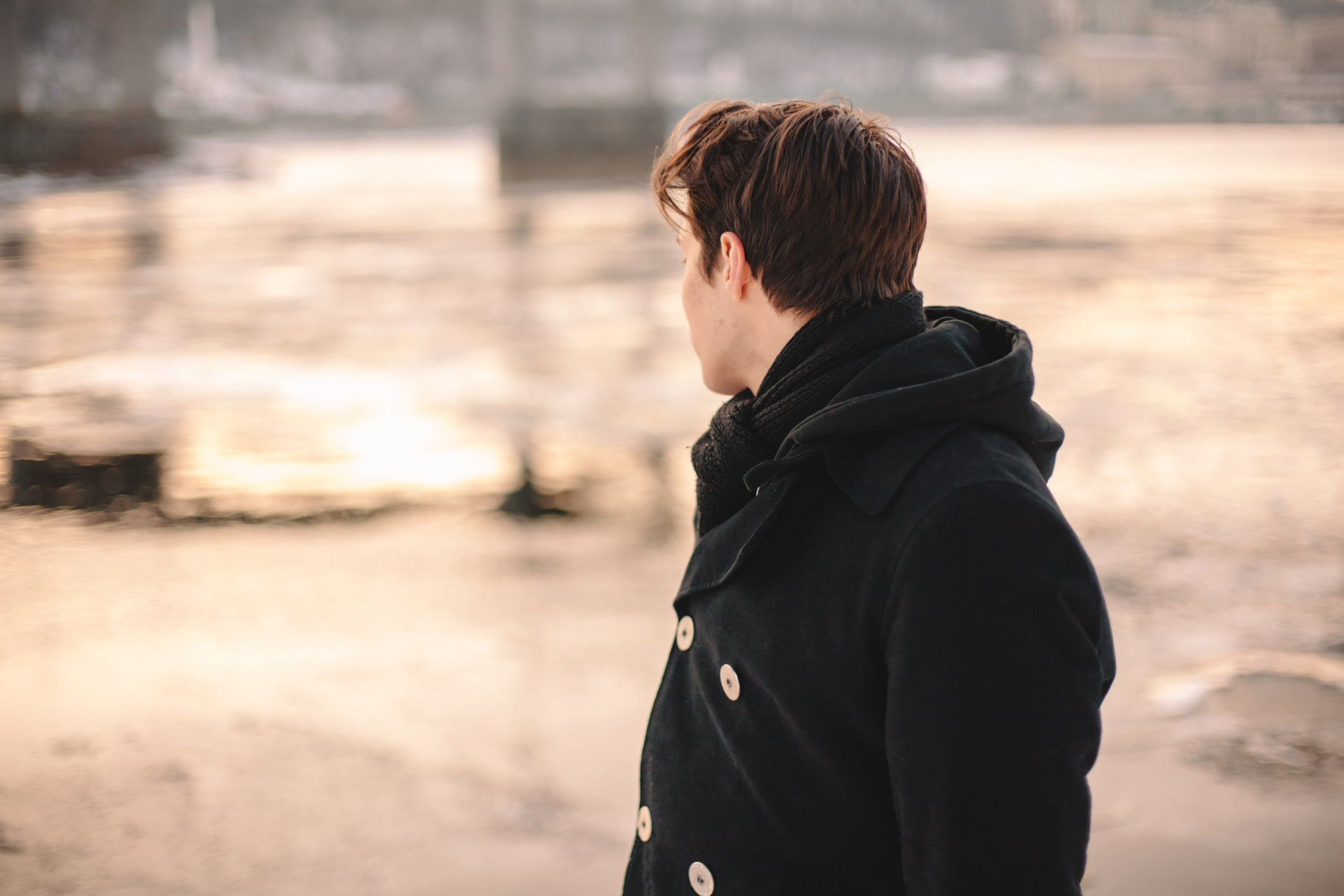 Teenage boy looking on river while standing outdoors in winter